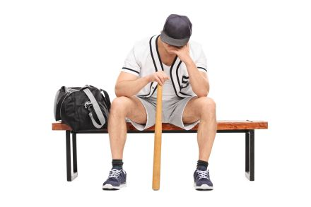 Sad young baseball player sitting on a bench